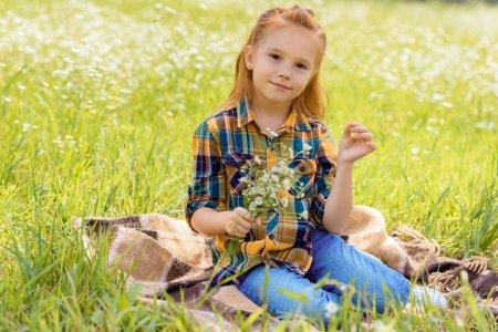 Foto de Sonriente niño con ramo de flores silvestres en Prado - Imagen libre de derechos