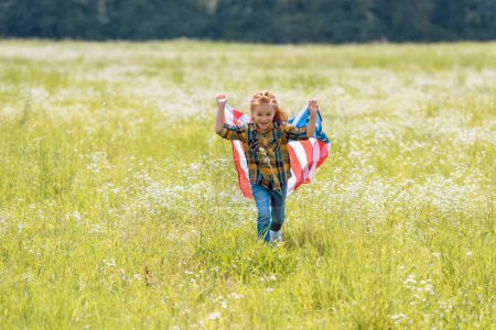 cheerful child running in field with american flag in hands
