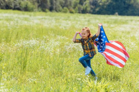 child running in field with american flag in hands