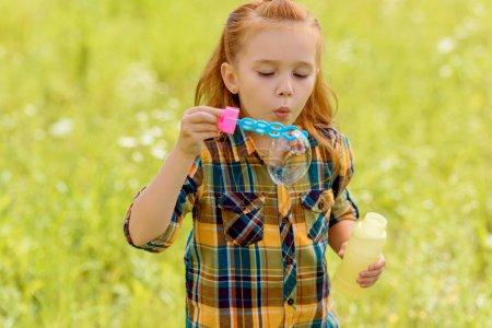 portrait of kid blowing soap bubbles in meadow