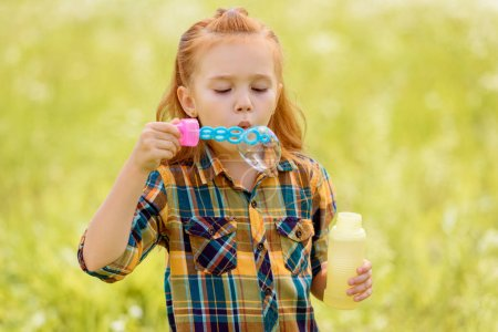 portrait of kid blowing soap bubbles in meadow