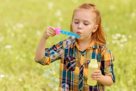 Photo for Portrait of kid blowing soap bubbles in meadow - Royalty Free Image