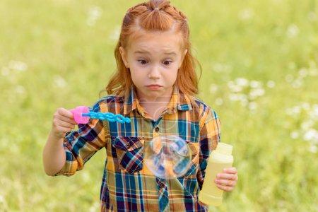 portrait of shocked kid blowing soap bubbles in meadow