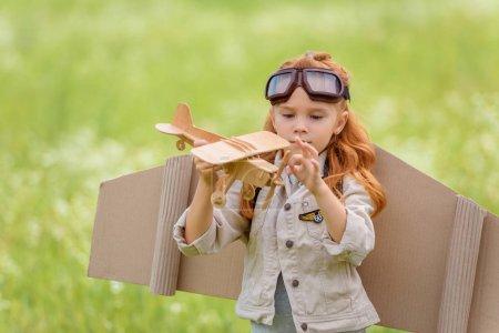 Photo pour Portrait de petit enfant en costume de pilote avec avion jouet en bois debout dans la prairie - image libre de droit