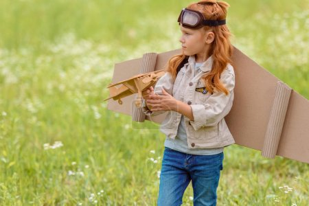 portrait of little child in pilot costume with wooden toy plane standing in meadow