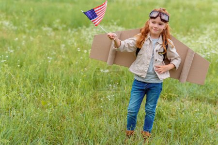 kid in pilot costume with american flagpole standing in meadow