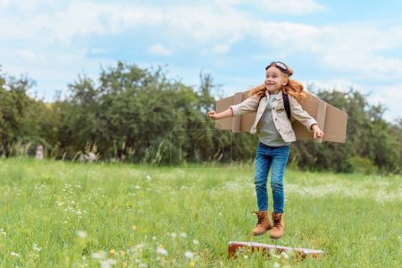 smiling kid in pilot costume jumping from retro suitcase in summer field