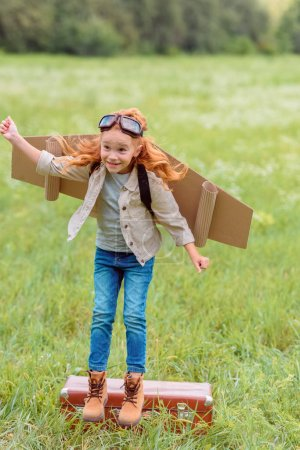 kid in pilot costume with outstretched arm jumping from retro suitcase in meadow