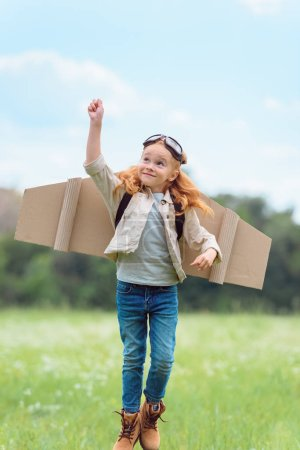 kid in pilot costume with outstretched arm jumping in meadow