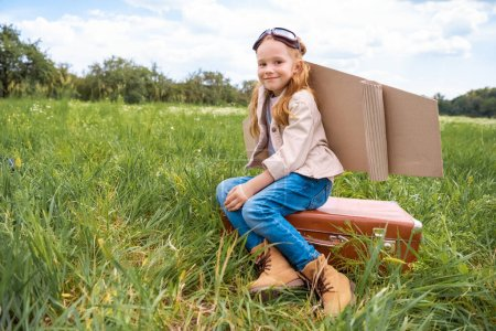 smiling cute kid in pilot costume sitting on retro suitcase in summer field