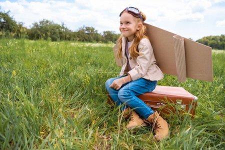 Photo pour Souriant mignon enfant en costume de pilote assis sur la valise rétro dans le champ d'été - image libre de droit