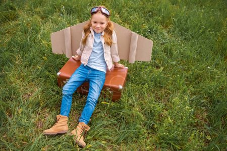 high angle view of smiling child with paper plane wings and protective eyeglasses resting on retro suitcase in meadow