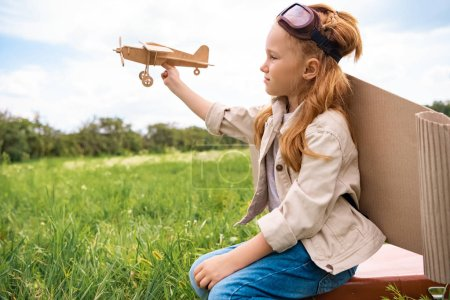 kid in pilot costume with wooden toy plane in hand sitting on retro suitcase in field