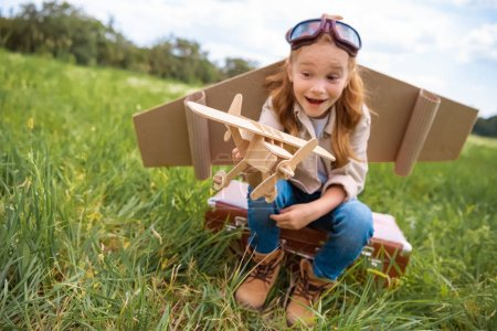 Photo pour Enfant émotionnel en costume de pilote avec avion jouet en bois à la main assis sur une valise rétro dans le domaine - image libre de droit