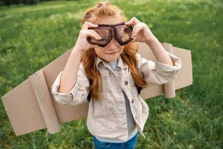 Photo for Portrait of little child in pilot costume wearing protective eyeglasses in summer field - Royalty Free Image
