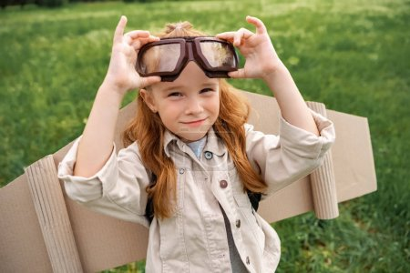 portrait of little child in pilot costume wearing protective eyeglasses in summer field