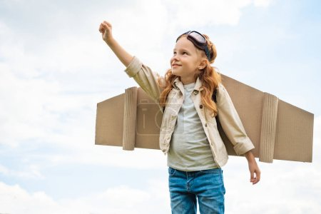 Portrait d'enfant ayant un avion en papier des ailes sur le dos et lunettes de protection sur la tête debout avec les bras tendu contre bleu ciel nuageux