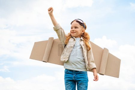 portrait of child with paper plane wings on back and protective eyeglasses on head standing with outstretched arm against blue cloudy sky