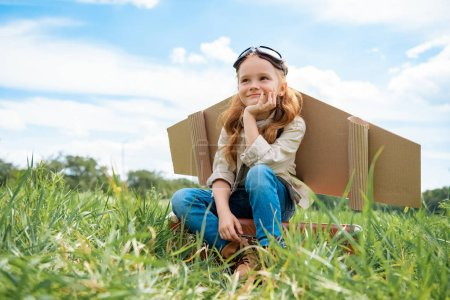adorable kid in pilot costume sitting on retro suitcase in summer field with blue cloudy sky on background