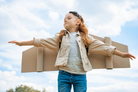 low angle view of child with paper plane wings and protective eyeglasses with outstretched arms against blue cloudy sky