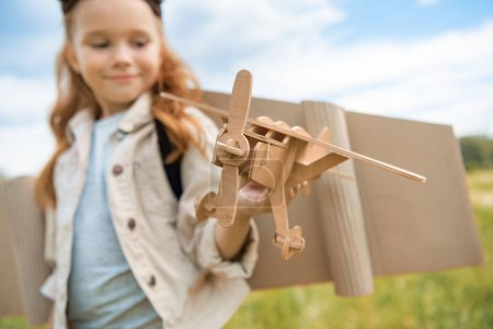 selective focus of red hair kid in pilot costume holding wooden plane against blue sky