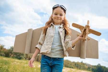 portrait of smiling red hair kid in pilot costume holding wooden plane in summer field