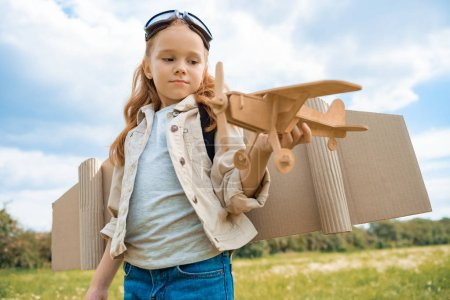 portrait of red hair kid in pilot costume holding wooden plane in summer field
