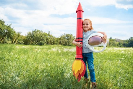 smiling red hair kid with rocket and astronaut helmet standing in summer field