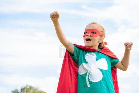 adorable child in superhero costume with outstretched arm and blue cloudy sky on background