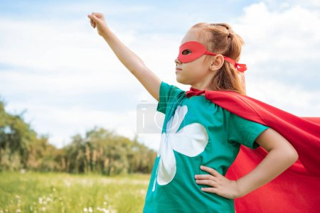 adorable child in superhero costume with outstretched arm in summer field