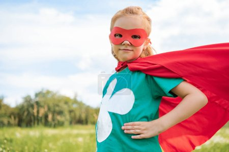 portrait of little child in red superhero costume standing akimbo in summer meadow