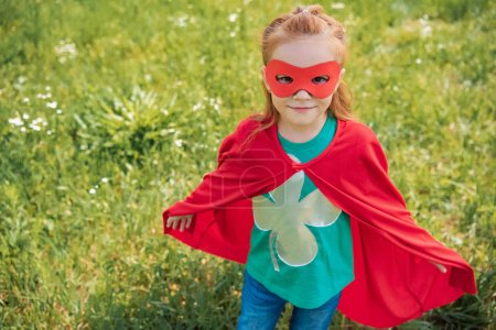 cute child in red superhero mask and cape standing in summer field