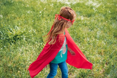 little child in red superhero costume standing in summer field