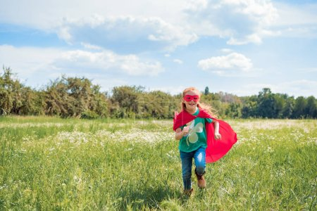 cheerful kid in red superhero cape and mask running in meadow on summer day