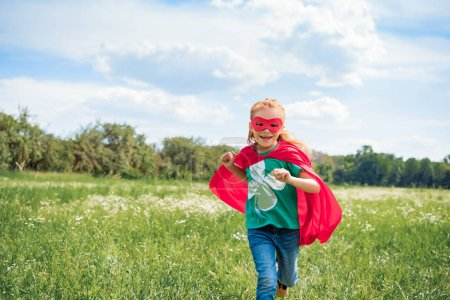 happy kid in red superhero cape and mask running in meadow on summer day