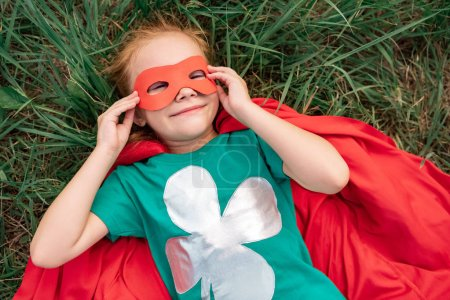 overhead view of kid in red superhero cape and mask lying on green grass