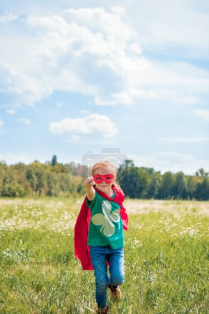 little kid in red superhero cape and mask with outstretched arm running in meadow on summer day