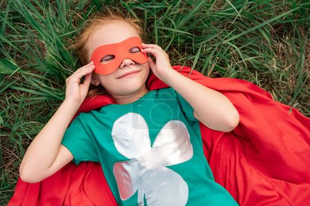 overhead view of kid with eyes closed in red superhero cape and mask lying on green grass