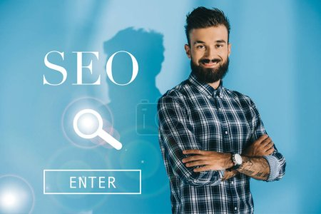 successful bearded developer posing with crossed arms, on blue with SEO search