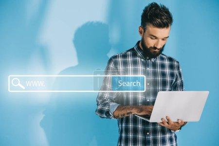 Photo pour Barbu développeur utilisant l'ordinateur portable, le bleu avec la barre de recherche de site Web - image libre de droit