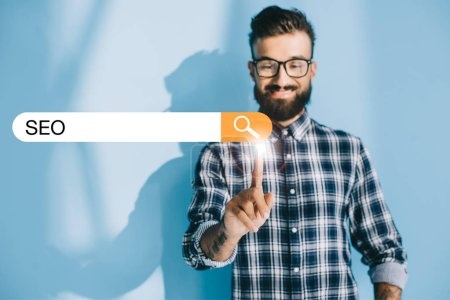 successful developer in checkered shirt pointing at SEO search bar