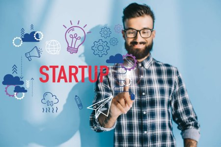 smiling businessman in checkered shirt pointing at startup icons