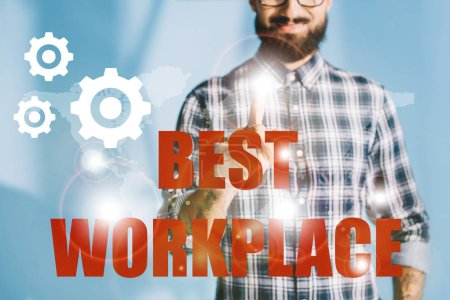 "cropped view of businessman in checkered shirt pointing at ""best workplace"" with gears"