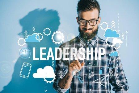 Photo pour Homme d'affaires souriant en chemise à carreaux pointant vers les icônes du leadership - image libre de droit