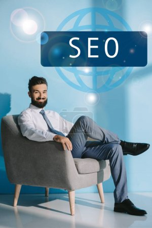 successful developer in formal wear sitting in grey armchair, on blue with SEO sign
