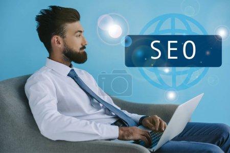 Photo pour Barbu développeur à l'aide d'ordinateur portable et assis dans le fauteuil, le bleu avec le signe de la Seo - image libre de droit