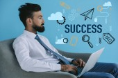 bearded businessman using laptop and sitting in armchair, on blue with success icons