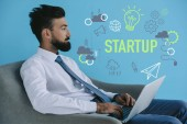 bearded businessman using laptop and sitting in armchair, on blue with startup icons and light bulb