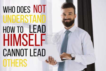 "bearded smiling businessman using laptop near window with ""who does not understand how to lead himself cannot lead others"""