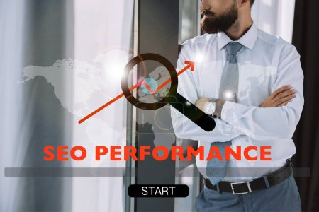 cropped view of developer with crossed arms standing near window with SEO performance and search sign